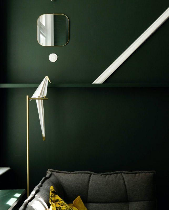Grön vägg bakom grå soffa
